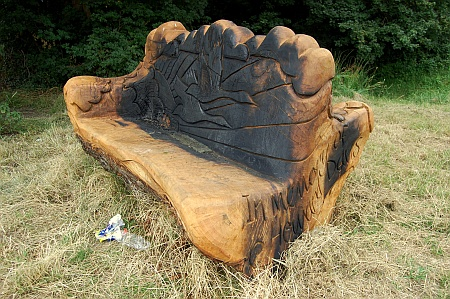 A fire-damaged carved wooden seat on Jubilee Green, Bradley Stoke