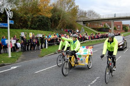 Pupils from Wheatfield Primary School cheer the rickshaw along Bradley Stoke Way.