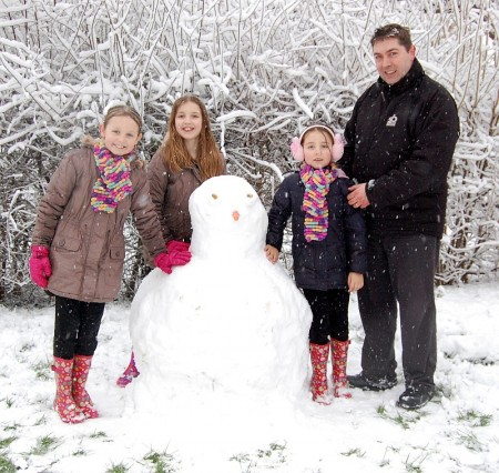Darcy, Felicity, Penelope and dad Kevin with their snowman in Wheatfield Drive.