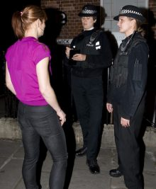 Library image of a woman being questioned by police officers.
