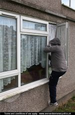 A man in a hooded top climbing in through an open window.