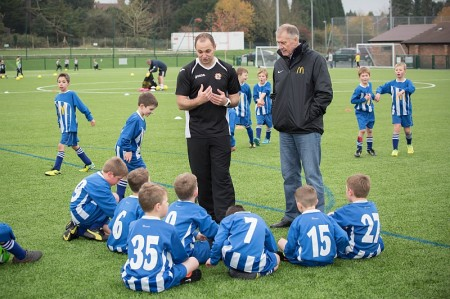 Sir Geoff Hurst watches Bradley Stoke Youth FC coach Jim Murdoch working with the U8 squad.