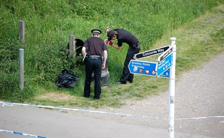 Police search a litter bin in the Three Brooks Local Nature Reserve, Bradley Stoke.