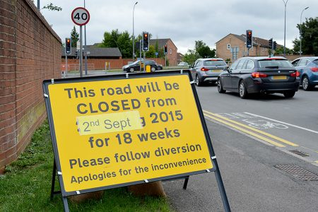 Roadside sign announcing closure of Woodlands Lane for 18 weeks from 2nd September.