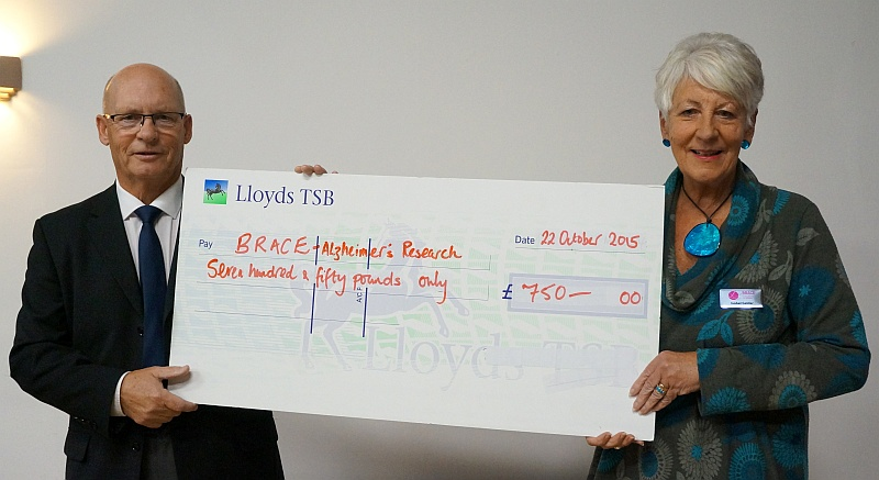 Isobel Gelder, of dementia research charity BRACE, receiving a cheque for £750 from Bradley Stoke Cricket Club captain George Eland.