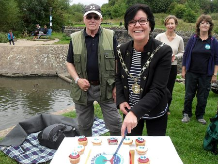 Cllr Erica Williams cuts the Three Brooks Nature Conservation Group's tenth birthday cake.
