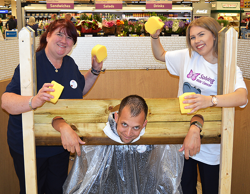 Tesco Extra Bradley Stoke staff members Dawn Richards (community champion, left) and Katie Palmer (right) invite shoppers to throw wet sponges at Atilla Kiss (home delivery manager) to raise funds for the Kisses for Kaylum appeal.