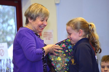 Christine Dursley, headteacher of Wheatfield Primary School, receives a gift from a pupil at a special assembly to mark her retirement after 18 years in the post.