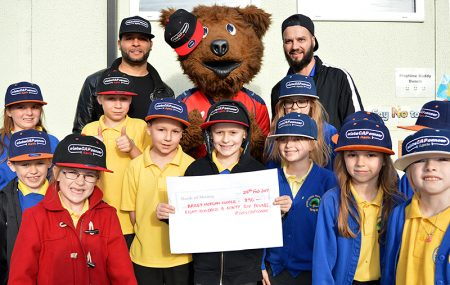 Photo of Bailey Cooper holding a cheque, accompanied by staff and pupils.