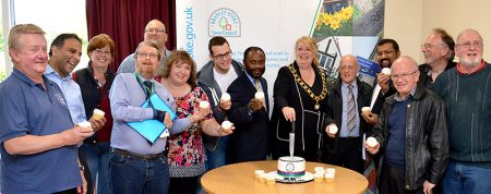 Photo of mayor Elaine Hardwick cutting a cake to mark the 25th anniversary of Bradley Stoke Town Council, watched by other members of the council.