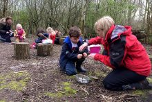 Photo of BSCS Catkins class learning in the forest school area.