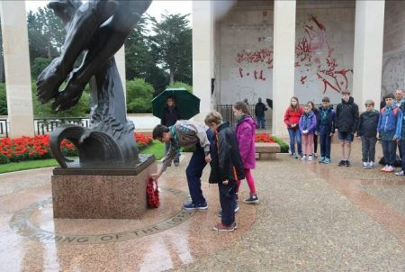 Members of the 1st Bradley Stoke Scout Group lay a wreath at the Normandy American Cemetery.