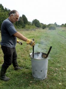 photo of a volunteer incinerating ash cuttings.