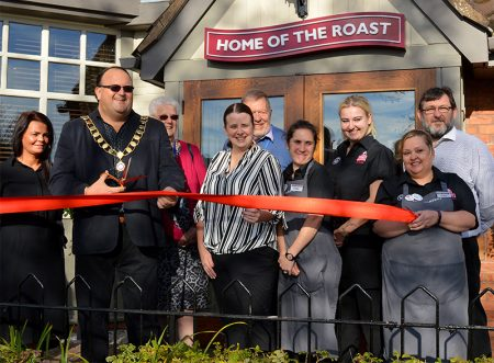 Photo of Cllr Andy Ward cutting the ribbon to reopen the Toby Carvery, watched by members of staff and volunteers from St Peter's Hospice.