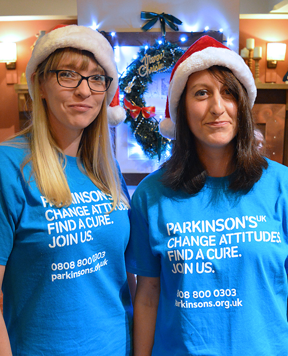 Photo of Karen Taylor (left) and Vicky Lovell in Santa hats and Parkinson's UK T-shirts.