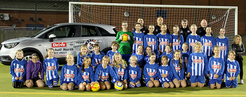 Photo of the girls' teams wearing match kit sponsored by Drive Vauxhall Bristol North.