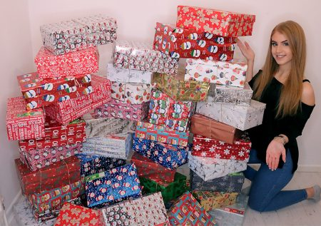 Photo of Ellie Harriss with the 44 shoeboxes she collected.