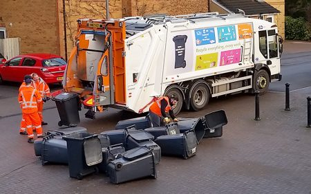 Photo of black refuse bins being collected.