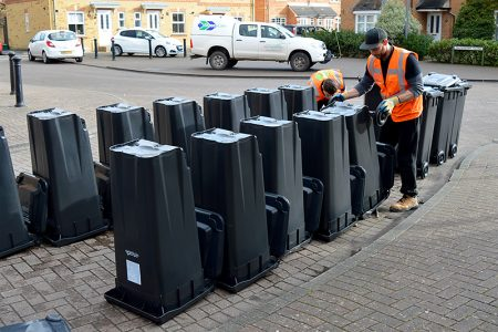 Photos of new, smaller black bins lined up on a street in Bradley Stoke.