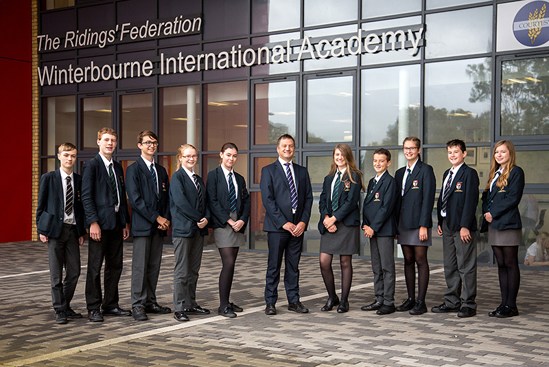 Photo of acting headteacher Peter Smart with students at Winterbourne International Academy.