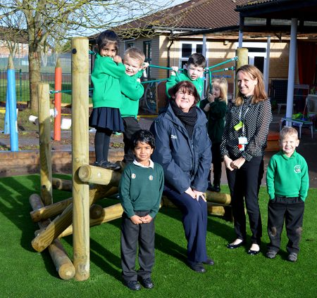 Photo of Tesco community champion Dawn Richards (seated) with Reception teacher Wendy Collins and pupils.