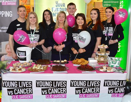 Photo of staff standing behind the cake sale stand outside the Specsavers store.