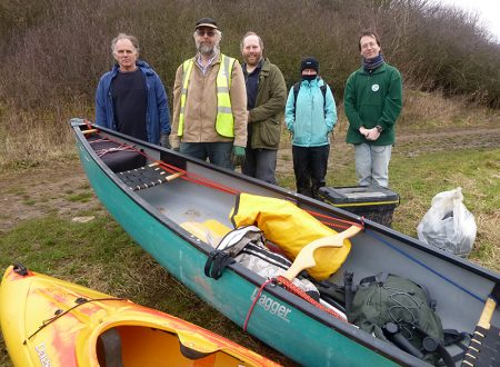 Photo of volunteers standing behind canoes used to collect rubbish from the lake.