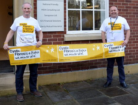 Photo of Neil Thompson and Wayne Carter holding a Cystic Fibrosis Trust banner outside the National Friendly office