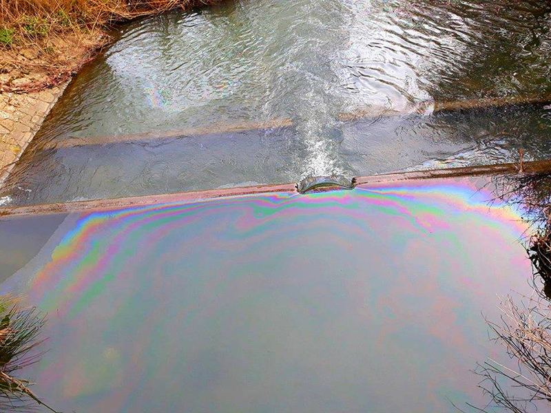 Photo showing a rainbow sheen on the surface of the water at one of the weirs on Stoke Brook.