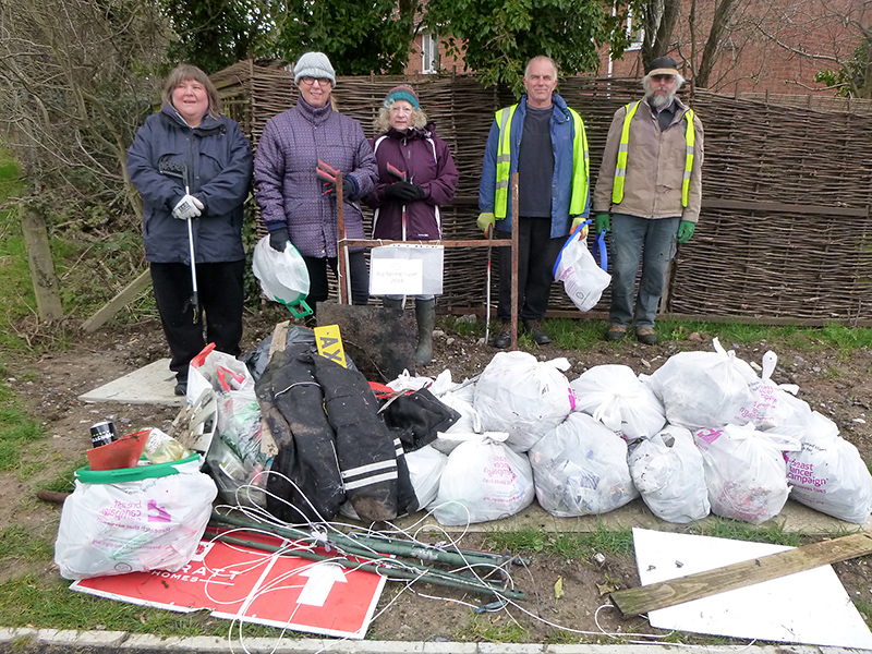 Photo of BSiB volunteers standing behind an assortment of rubbish that they collected during their Big Spring Clean.