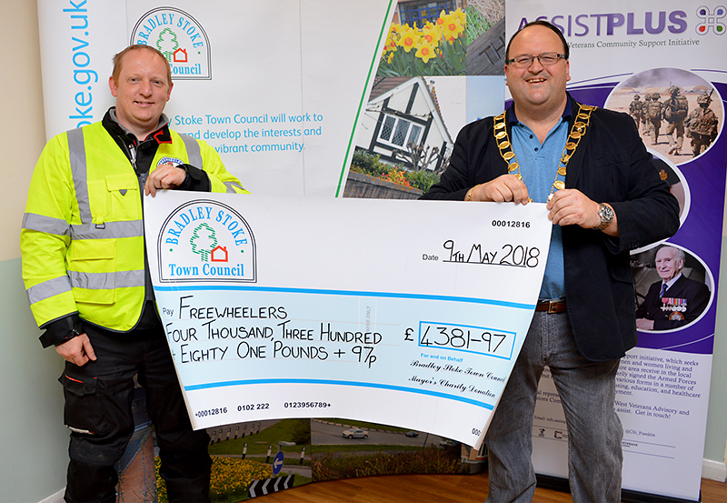 Photo of Cllr Andy Ward presenting a charity cheque to Matt Eager, fundraiser and rider for Freewheelers EVS.