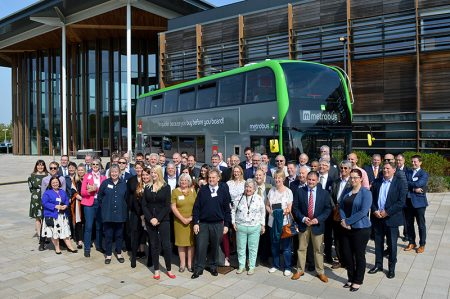 Photo of a crowd of dignitaries standing in front of a MetroBus vehicle at the M3 Route launch event.