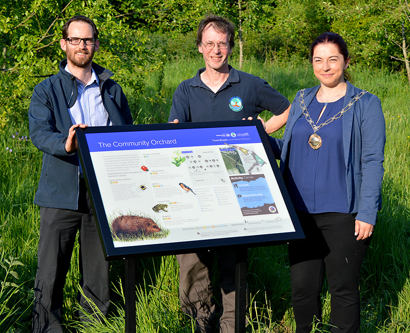 Photo of the panel unveiling in the community orchard. L-r: Jamie Bowkett (senior ecologist, Wessex Water), Robin Jones (chair, Three Brooks Nature Conservation Group) and Cllr Rachel Hunt (chair, South Gloucestershire Council).