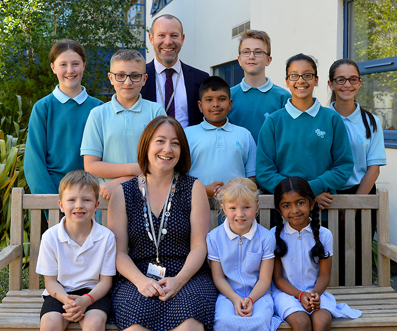 Photo of BSCS staff and students. Standing is Steve Moir (headteacher); seated is Sharon Clark (head of primary phase).