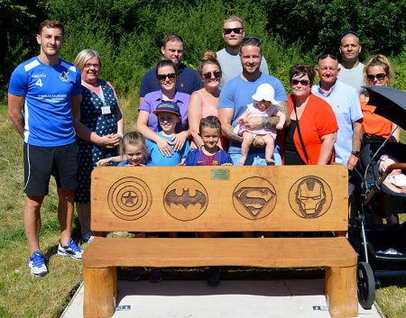 Photo of the 'celebration bench' after its unveiling, with family and friends standing behind.