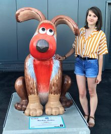 Photo of Hannah Bone with Rockin' Robin, the giant Gromit figure she painted for the Gromit Unleashed 2 arts trail.