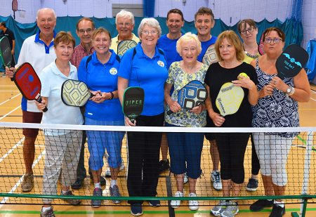 Photo of a group of pickleball players standing behind a net.