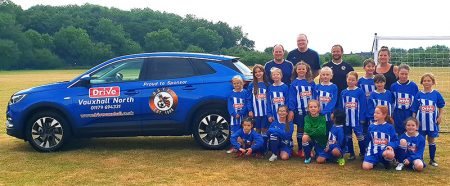 Photo of the BSYFC U9 Girls in their match kit sponsored by Drive Vauxhall Bristol North standing next to a Vauxhall Crossland X vehicle .