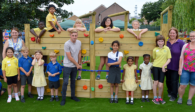 Photo of former pupil Joe Morrell cutting a ribbon on one of the new pieces of climbing equipment.