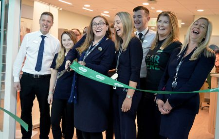 Photo of a member of staff cutting a ribbon to mark the opening of the updated store.