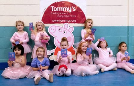 Photo of Babyballet Bradley Stoke pupils with the Tommy's charity logo on a wall behind them.