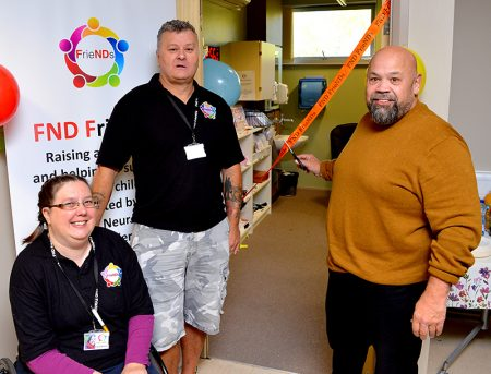 Photo of Gareth Chilcott cutting a ribbon to open the FND FrieNDs office, watched by Lucy Skinner and Kevin Clark.