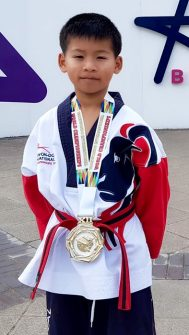 Photo of Nathan Wong wearing his world championship gold medal.