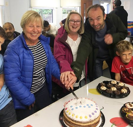 Photo of Chris Dursley, Lois Haydon and Phil Winterburn cutting the cake.