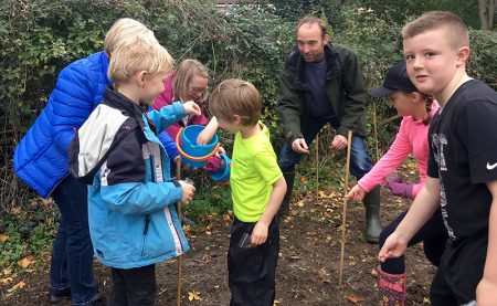 Photo of children and adults scattering wildflower seeds.