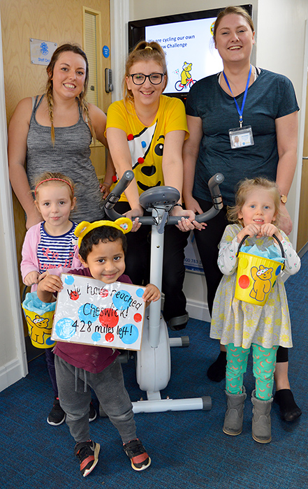 Photo of a member of staff on an exercise bike, surrounded by other members of staff and children.