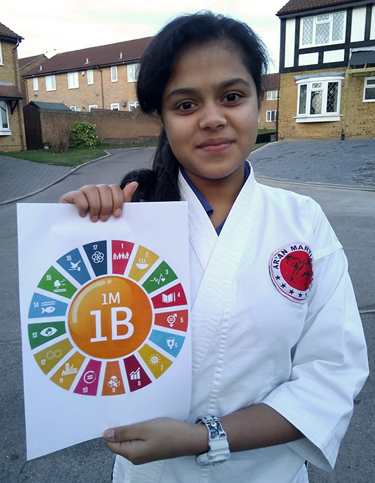 Photo of Khushi Ashwin holding a poster showing the 17 UN sustainable development goals on which the 1M1B programme is based.