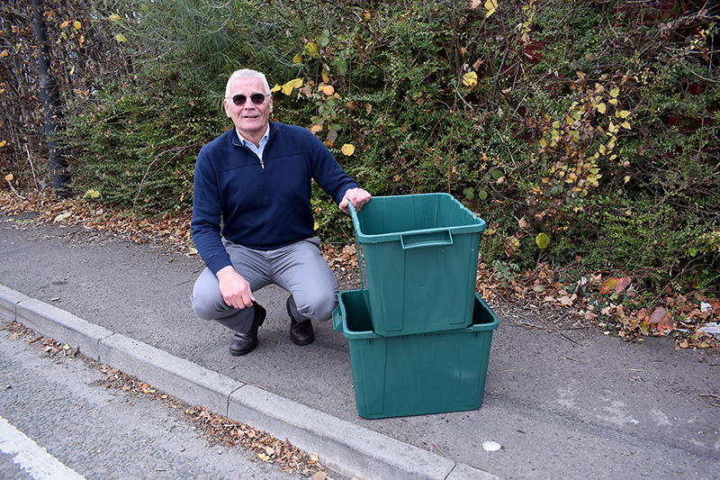 Photo of Cllr Paul Hughes with green recycling boxes.