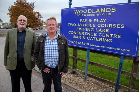 Photo of Bradley Stoke South ward councillors Roger Avenin (left) and John Ashe standing in front of a sign at the entrance to Woodlands Golf & Country Club.