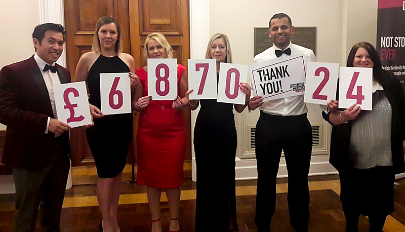 Specsavers staff hold up cards showing the amount they have raised for CLIC Sargent.